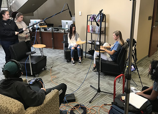 Group of students with video, lighting, and audio equipment filming two other students sitting down