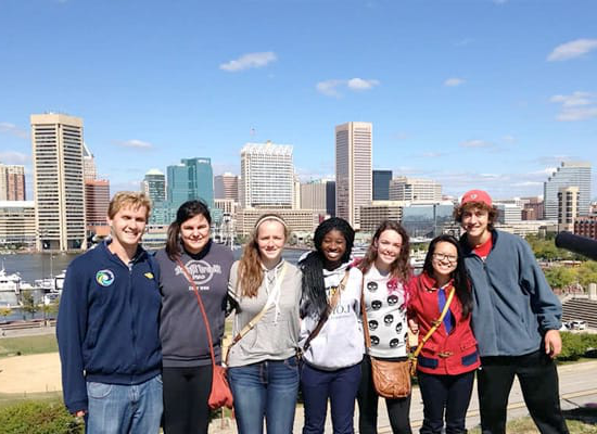 A group of students posing for a photo, with the harbor and Baltim要么e skyline in the background