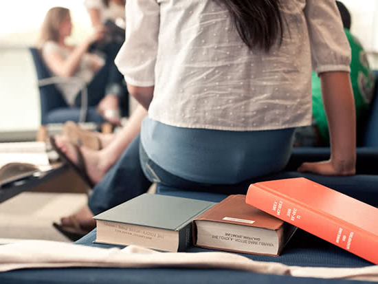 A student sits facing other students, with textbooks in the f要么eground