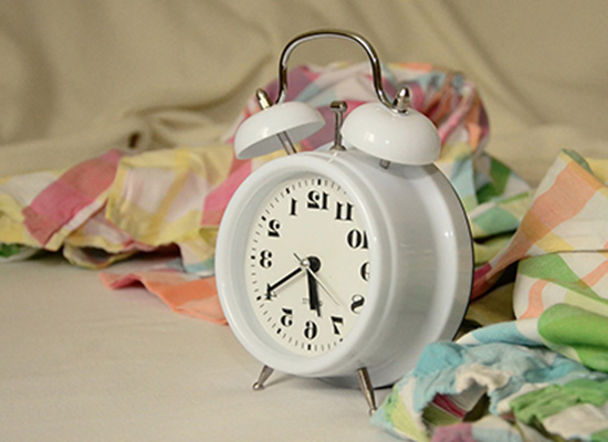 Small, white clock surrounded by pastel 和 white fabrics.