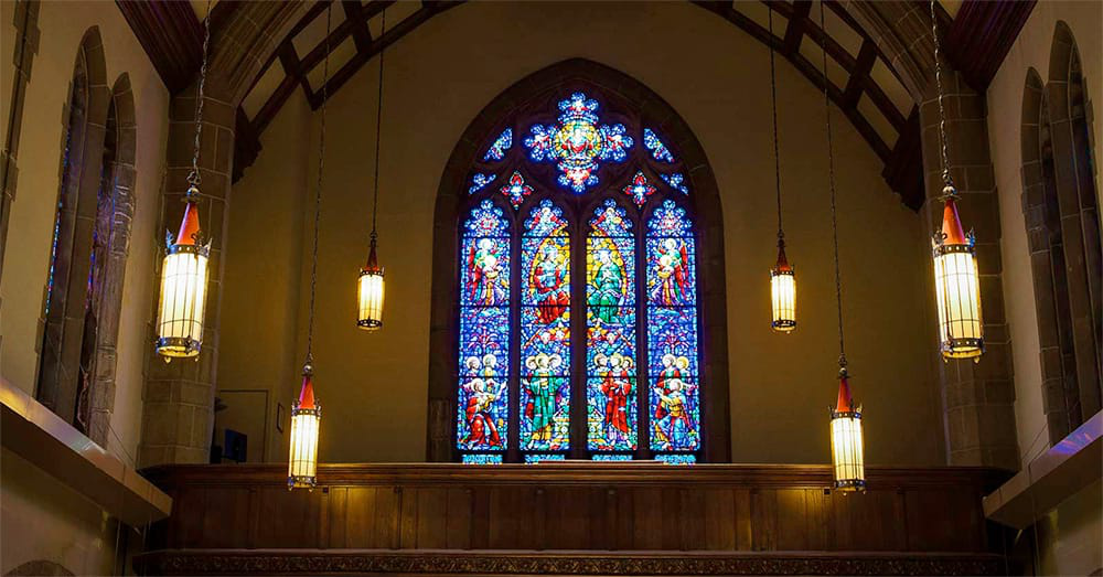 Stained glass and hanging lanterns light up the interior of the 校友 Memorial Chapel