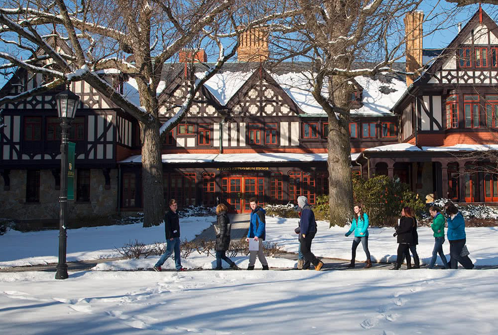 A line of visitors walks in front of the Humanities Building, a fresh blanket of snow covers the ground