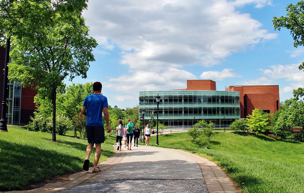 Students walking along a paved path, the library can be seen in the background