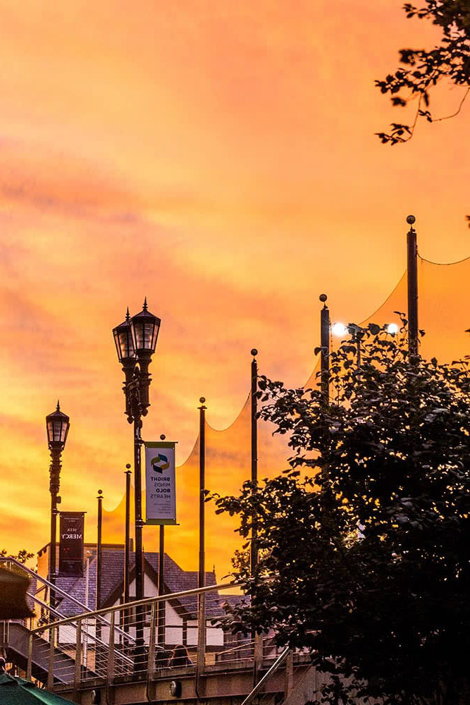 Silhouetted lamp posts and the Humanities Building set in front of an orange sunset
