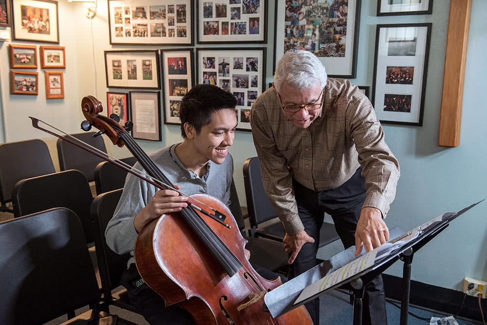 A professor points at music while a student sits nearby with a cello