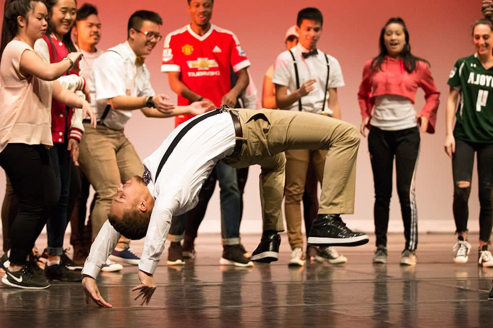 A student does a back flip on stage while other performing students cheer him on