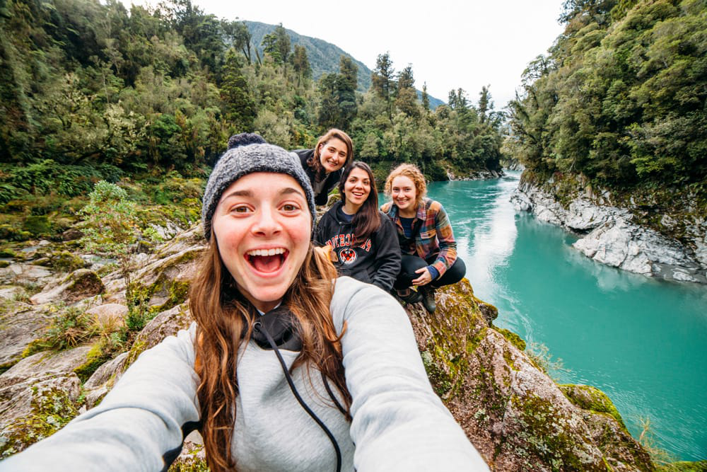 A student taking a selfie with other students in New Zealand - trees and a clear blue river can be seen in the background