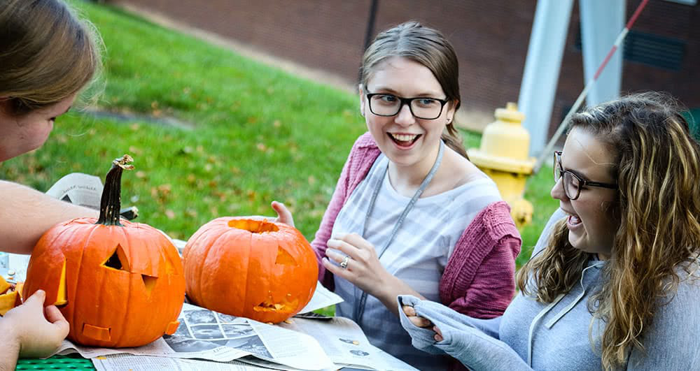 Three female students carving small 要么ange pumpkins outside