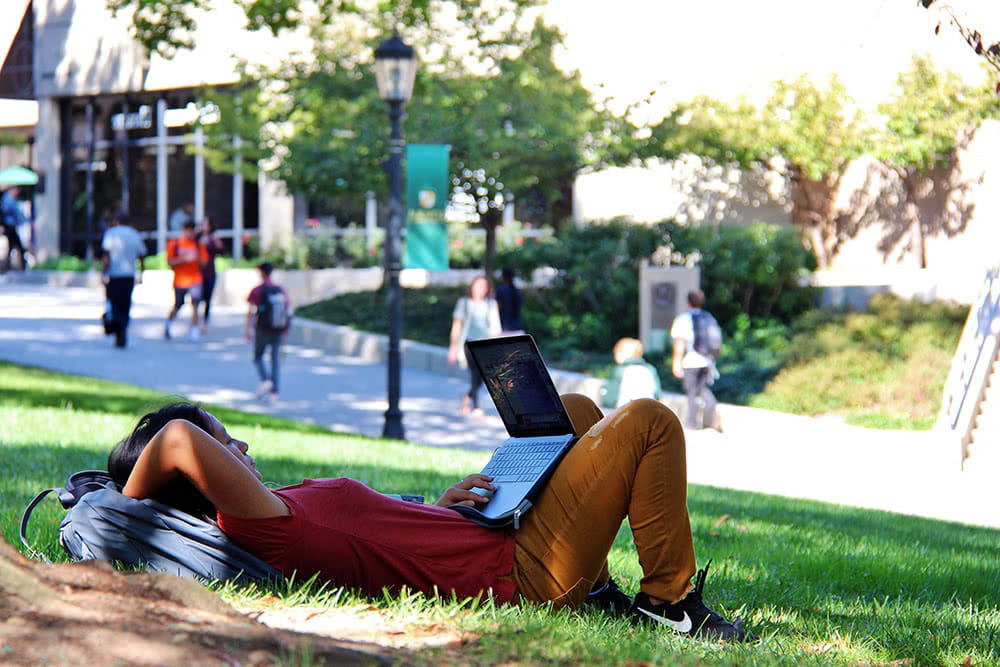 A student laying on the grass with a laptop in her lap