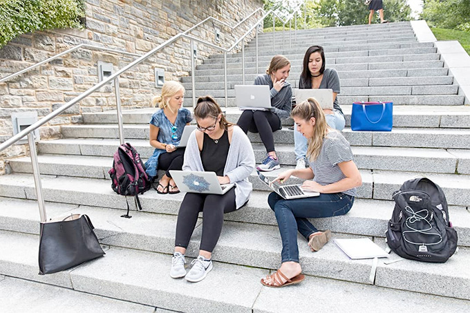 Students sit on steps outside with their laptops on a sunny day