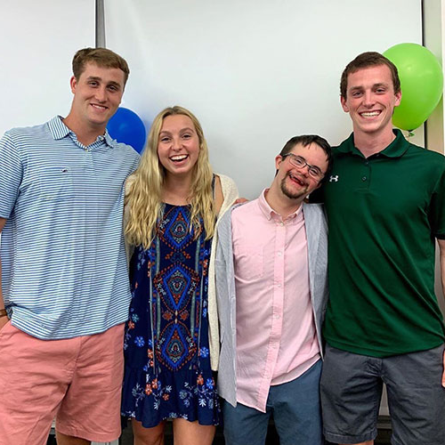 3 Loyola swimmers hang out with a friend from Club PALS Loyola during NCAA Inclusion Week