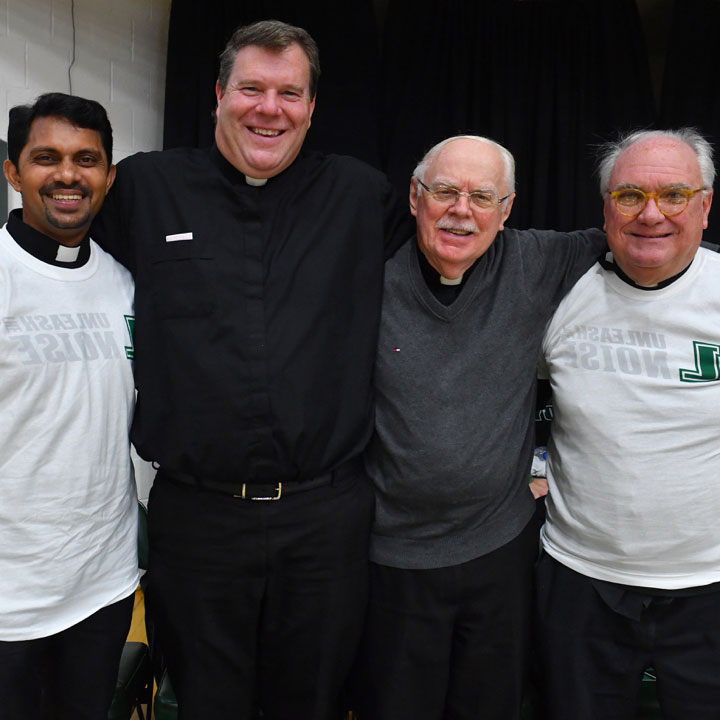 Jesuits at a basketball game in Loyola t-shirts