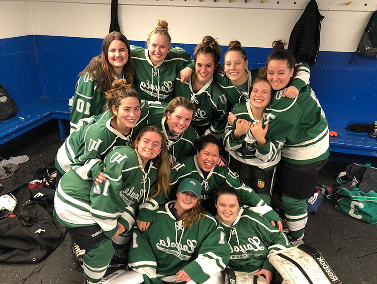 Loyola Women's Club Ice Hockey team smiling after a win.