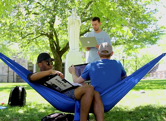 Students studying on the Quad while lounging in hammocks