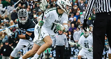 A Loyola lacrosse player with the ball runs past a Johns Hopkins player