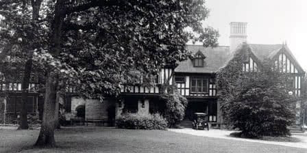 An old black and white photo of the Humanities Building, with a Ford Model T parked in front