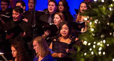 Students singing next to a Christmas tree