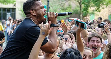 A performer sings in front of a crowd of students