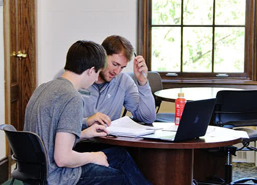 Two students working together a table in the Study