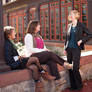 A professor talking with two students on the Humanities porch