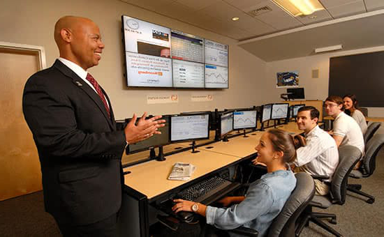 A professor teaching students in front of computer screens