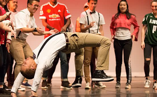 A student doing a flip during a dance performance